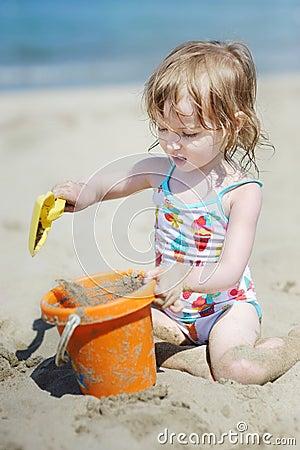 Cute little girl playing on a beach
