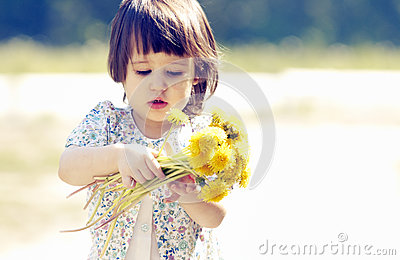 Cute little girl playing with a dandelion