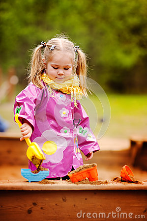 Cute little girl playing in a sandbox