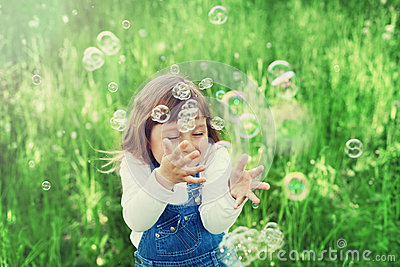 Cute little girl playing with soap bubbles on the green lawn outdoor, happy childhood concept, child having fun Stock Photo