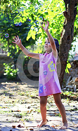 Cute little girl playing soap bubbles in the yard