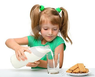 Cute little girl is pouring milk in glass