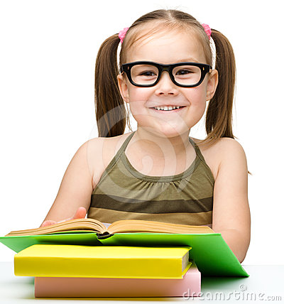 Cute little girl reads a book