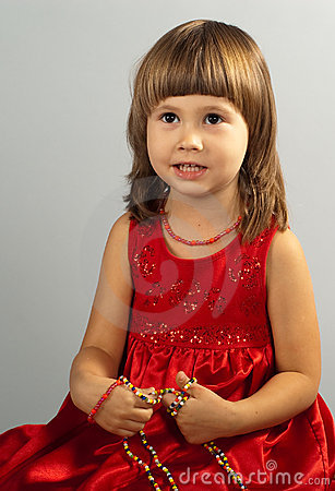 Cute little girl in a red dress with necklace in h