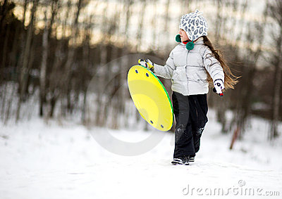 Cute little girl running in the snow with saucer