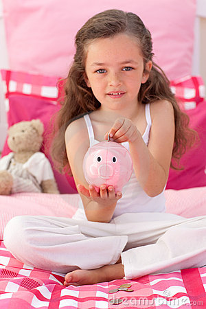 Cute little girl saving money in a piggybank