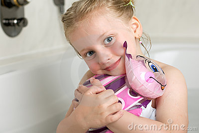 Cute little girl is sitting in bath tub with toy