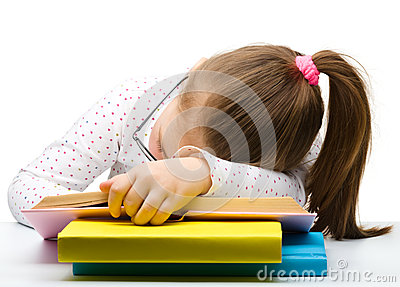 Cute little girl is sleeping on a book