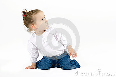 Cute little girl squatting on his knees and leaning with one hand on the ground looking up curiously