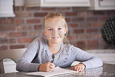 Cute little girl studying and writing