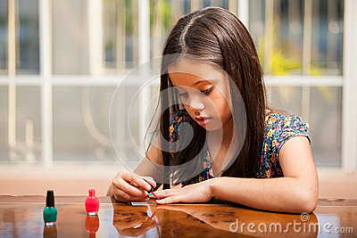 Cute little girl using nail polish