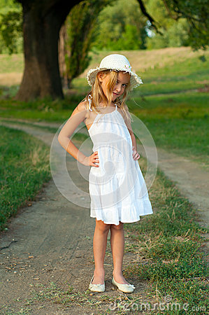 cute little girl in white dress and hat standing stock