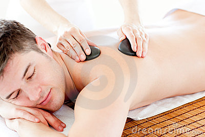 Cute man enjoying a back massage with hot stones
