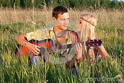 Cute man and fine woman sit on meadow