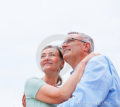 Cute mature couple hugging eachother against white
