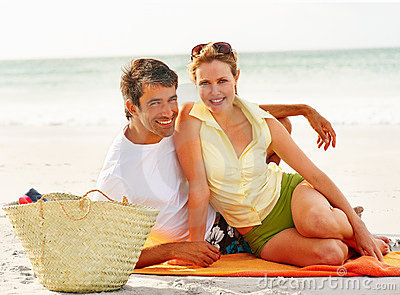 Cute mature couple smiling while at a beach picnic