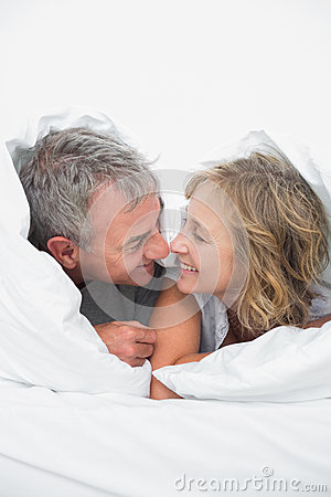 Cute middle aged couple under the duvet