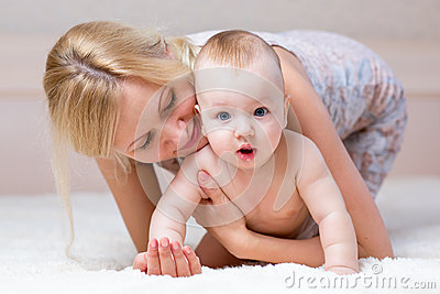 Cute mother playing with baby boy indoors