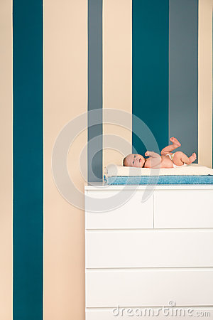 Cute newborn lying on a commode