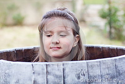 Cute pretty young girl hiding in a barrel