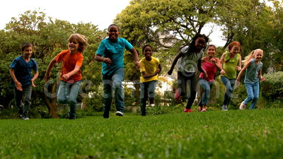 Cute pupils racing on the grass outside school. In slow motion stock video footage