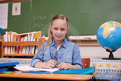 Cute schoolgirl doing classwork
