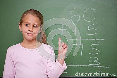 Cute schoolgirl raising her hand