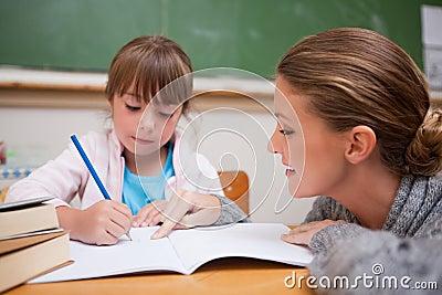 Cute schoolgirl writing a while her teacher is talking
