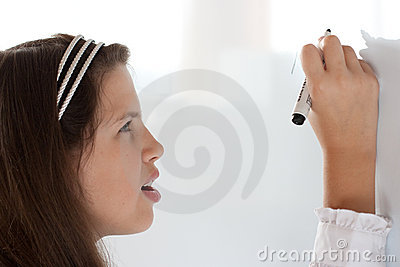 Cute schoolgirl writing letter on whiteboard