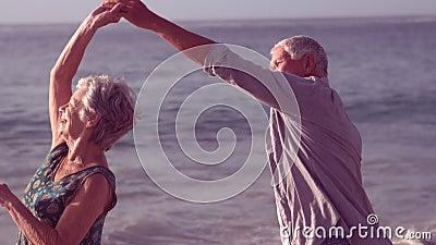 Cute senior couple dancing. On the beach