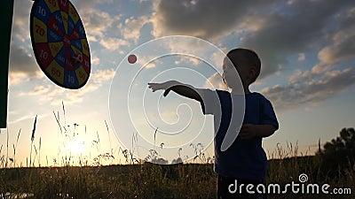 Cute silhouette van een vrolijke jongen die in langzame beweging velcro ballen op het doelwit gooit stock video