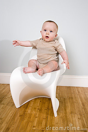 Cute six month old baby seated on a chair