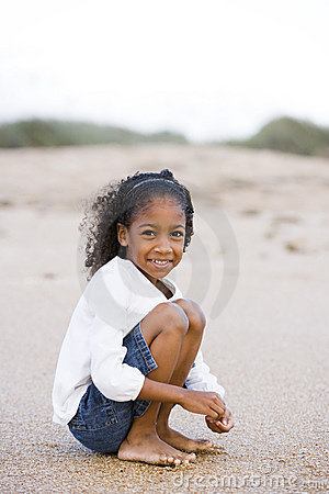 Cute six year old African-American girl on sand