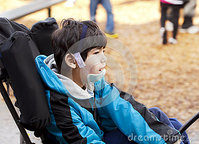 Cute six year old disabled boy in wheelchair on playground