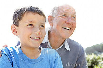 Cute small boy looking away with his grandfather