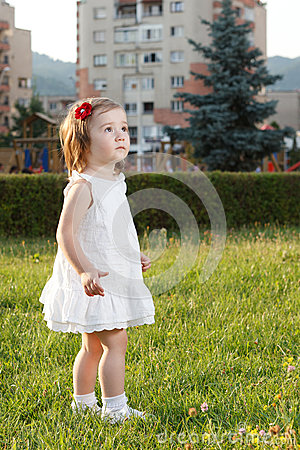 Cute small girl standing in grass