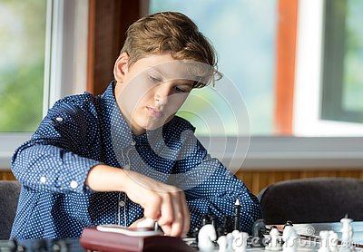 Cute, smart, 11 years old boy in shirt sits in the classroom and plays chess on the chessboard. Training, lesson, hobby, education Stock Photo