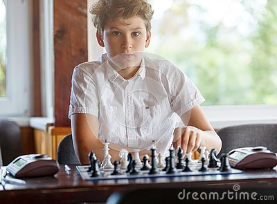 Cute, smart, 11 years old boy in white shirt sits in the classroom and plays chess on the chessboard. Training, lesson, hobby Stock Photo