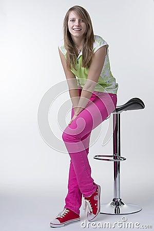 Happy girl sitting on a bar chair