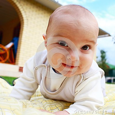 Cute smiling infant baby playing at the yard.