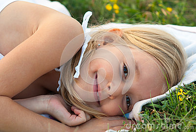 Cute smiling little girl lying on the blanket