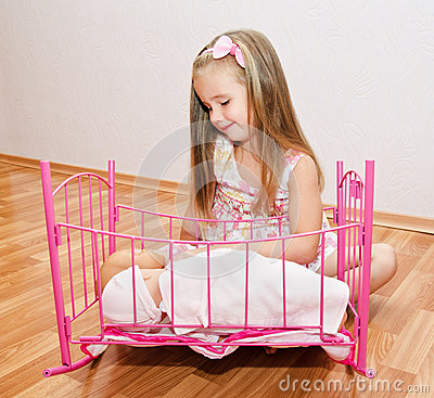 Cute smiling little girl playing with her newborn baby dolls
