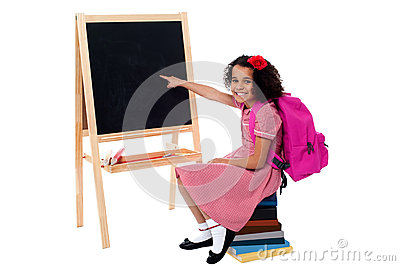 Cute smiling student pointing at blank chalkboard