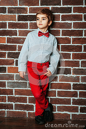 Free Cute Stylish Little Boy Staying Near The Brick Wall In Red Pants And Red Bow Tie. Kids, Boy Stock Photos - 79925563
