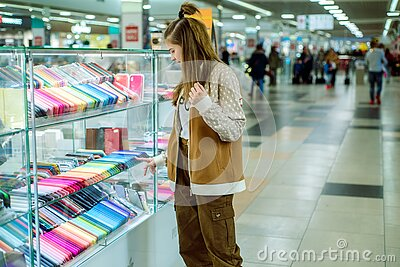 Cute teen girl chooses a mobile phone and protection for him. multi-colored phone cases in the mall. Shopping in the store, Stock Photo