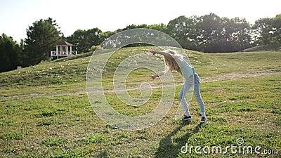 Cute teenage girl doing cartwheel at green meadow stock video footage
