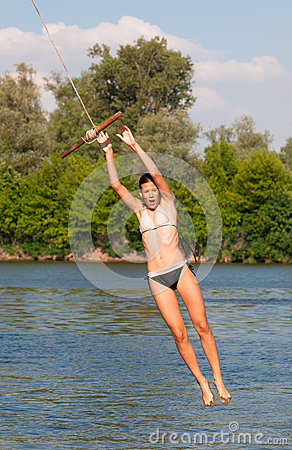 Cute teenage girl jumping into the river