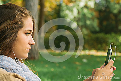 Cute Teenager Listening to Music on a Cell Phone