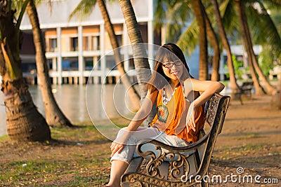 Cute Thai girl is relaxing near the riverside
