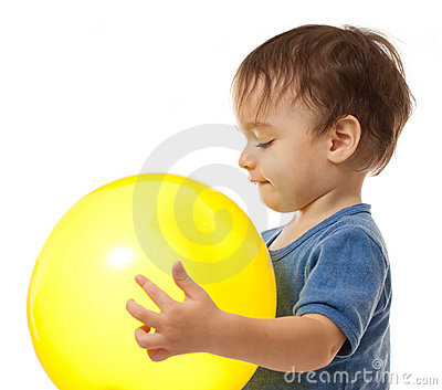 Cute toddler boy is playing with yellow balloon